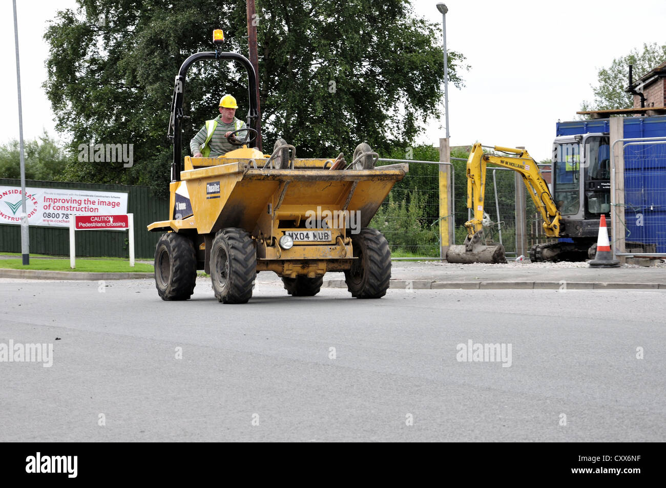 Construction worker driving small dumper on road with wheelbarrows - Stock Image