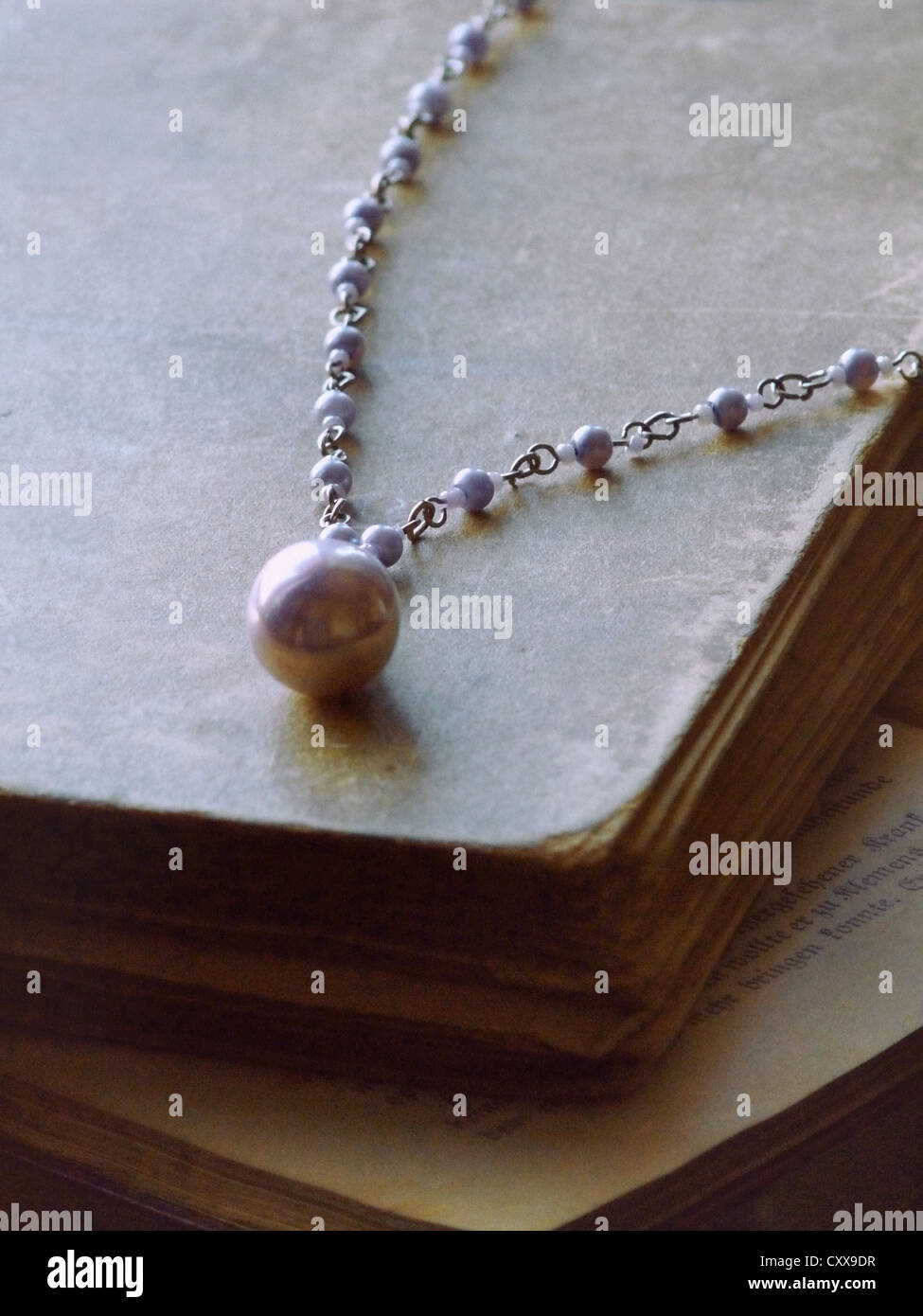 An old large violet pearl necklace laid on antique books. - Stock Image