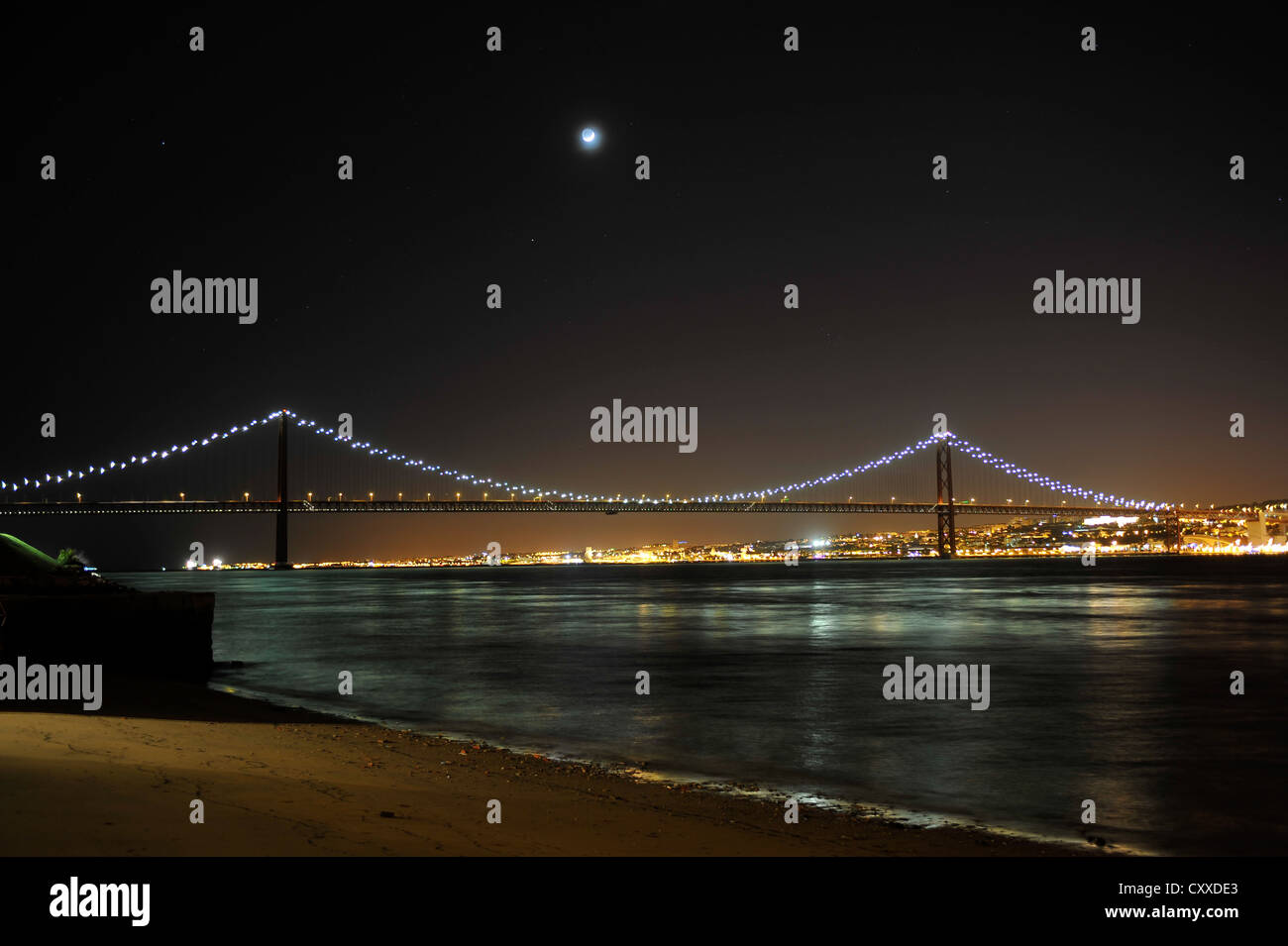 View of 25 de Abril Bridge and the suburb of Belem at night, as seen from Cacilhas, Portugal, Europe Stock Photo