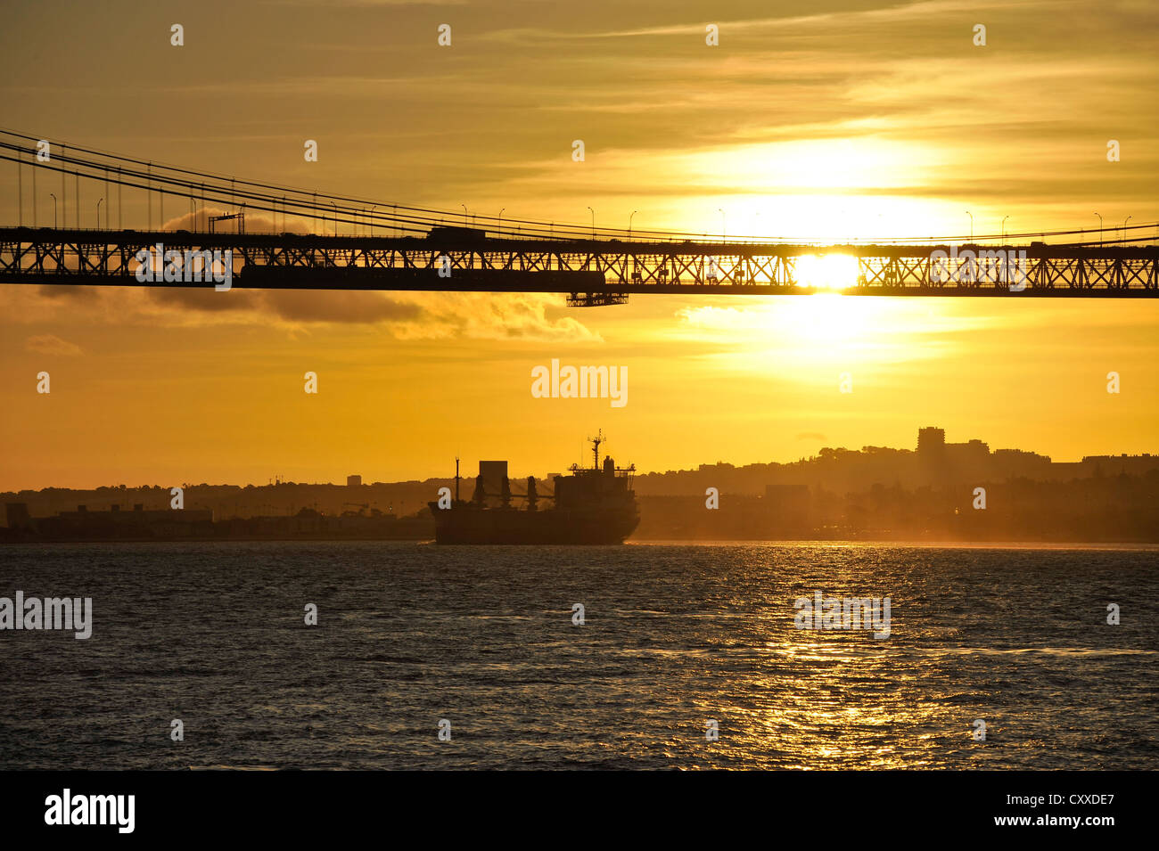 View of 25 de Abril Bridge and the suburb of Belem at sunset, as seen from Cacilhas, Portugal, Europe Stock Photo