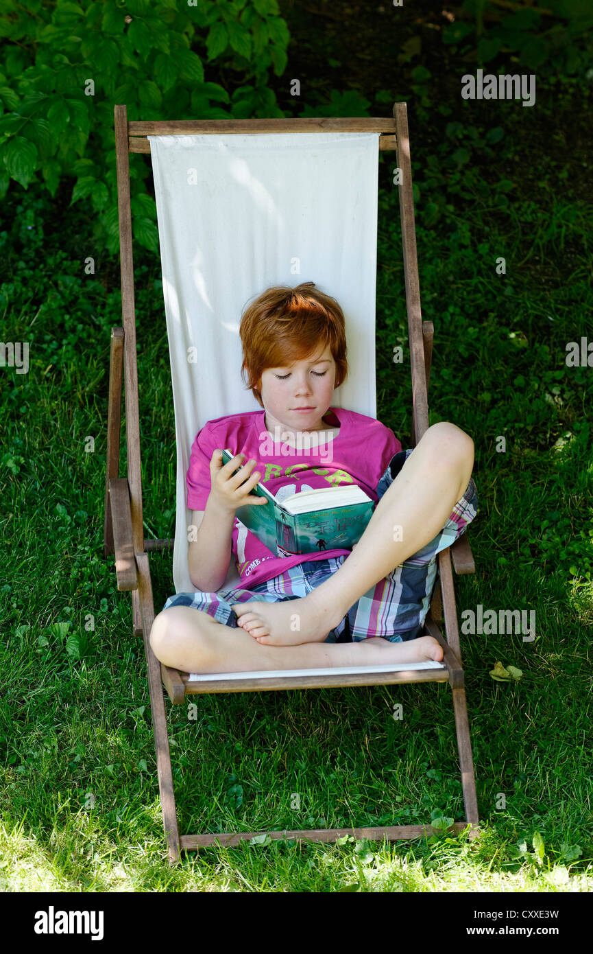 Child, boy, 11 years, reading a exciting holiday book whilst sitting in a deck chair in the garden - Stock Image