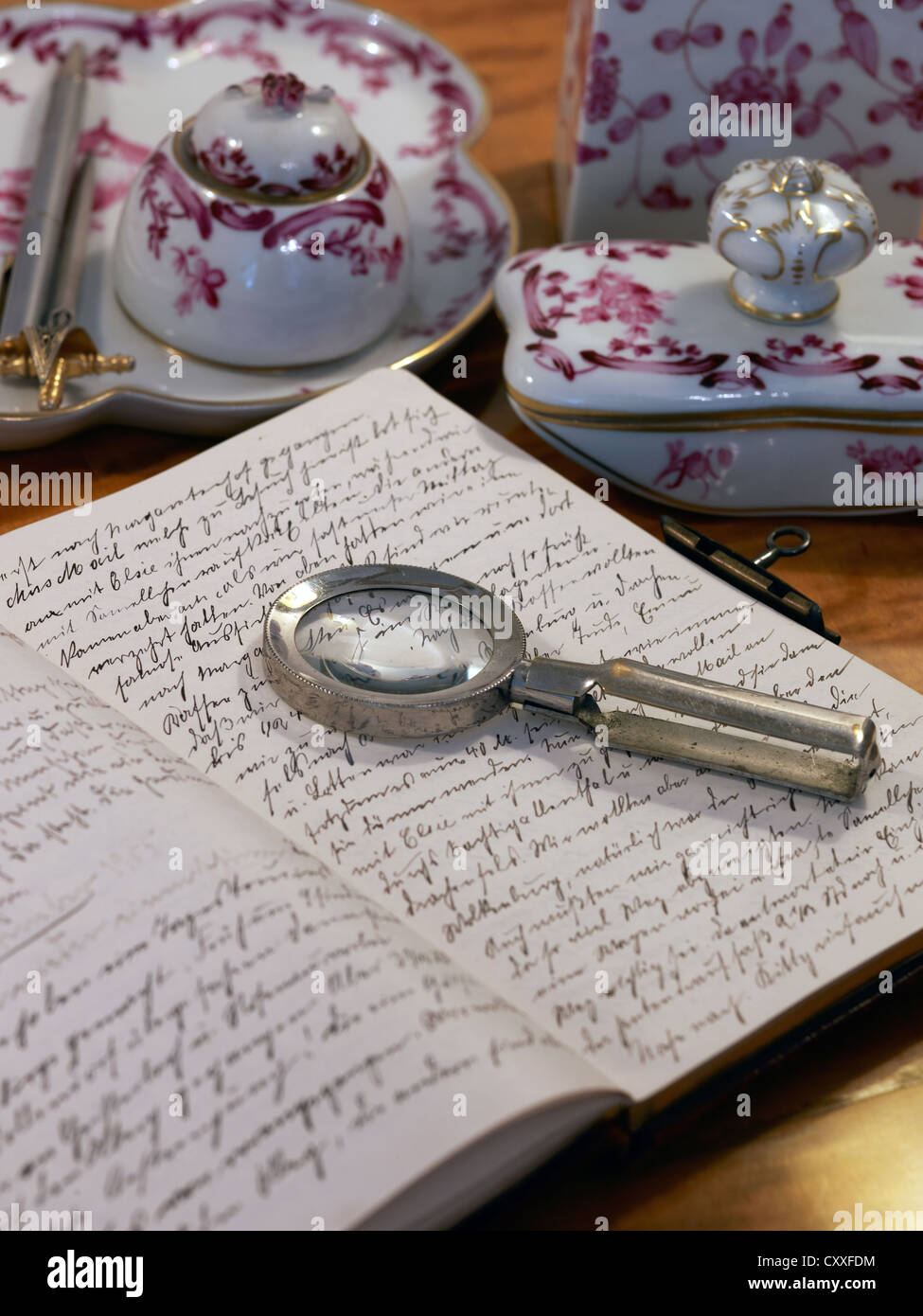 Still life with a handwritten diary, magnifying glass and antique bone china accessories - Stock Image