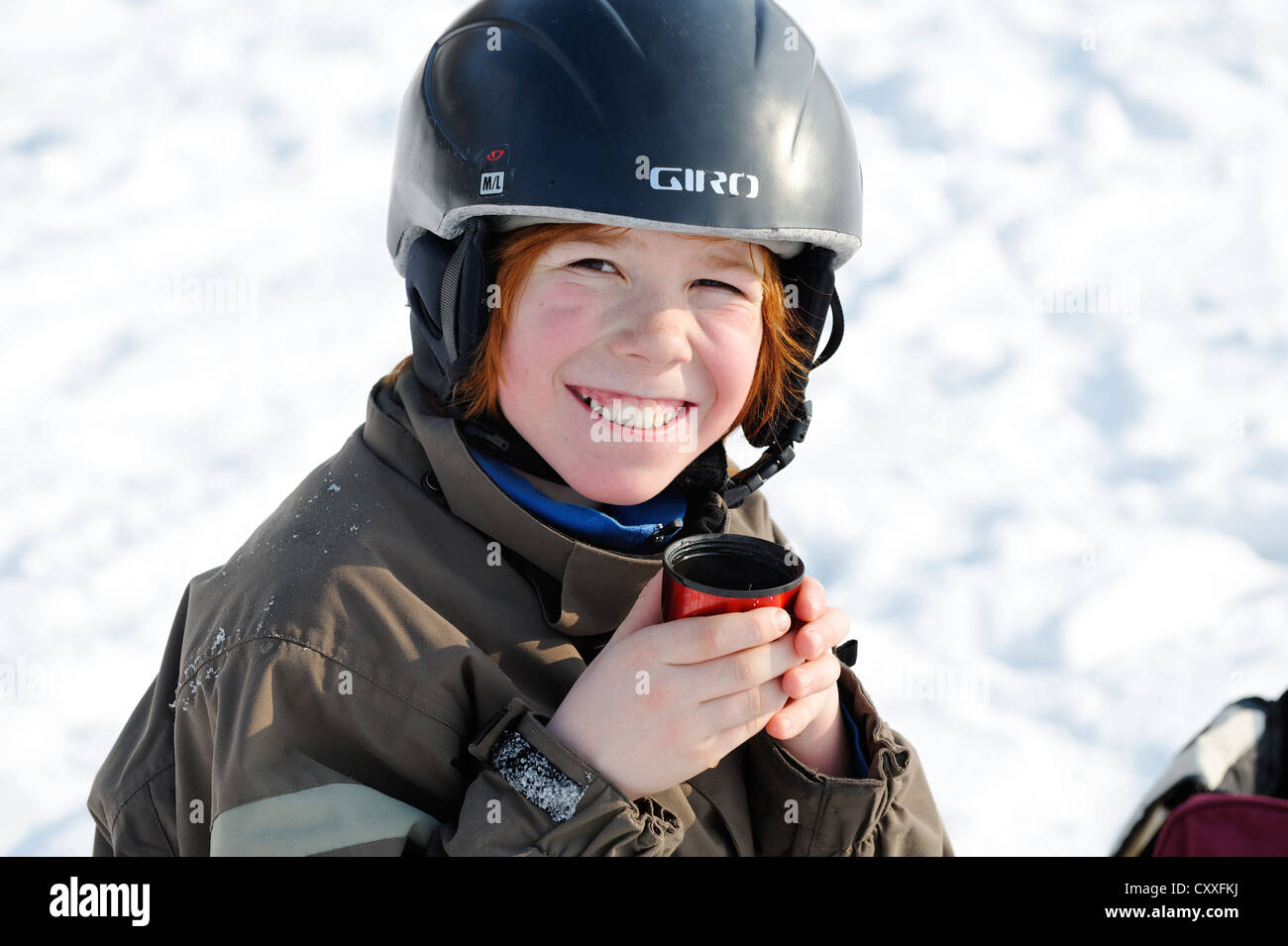 Boy drinking a cup of tea during wintersports in the snow - Stock Image