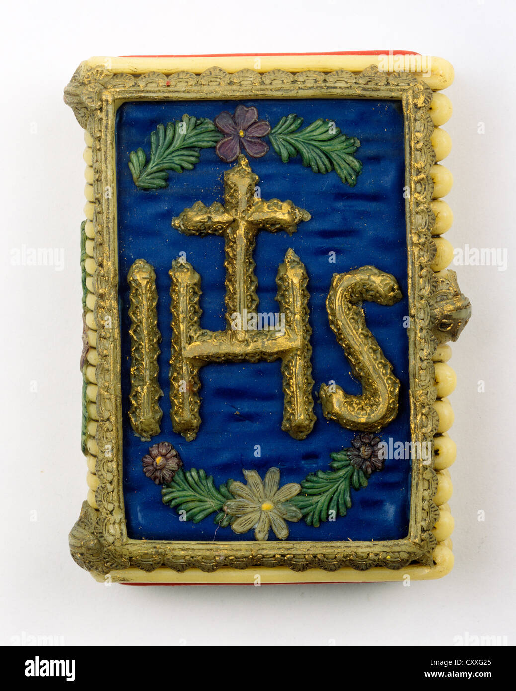 Wax taper in the shape of a book with the symbol of Jesus Christ, IHS - Stock Image