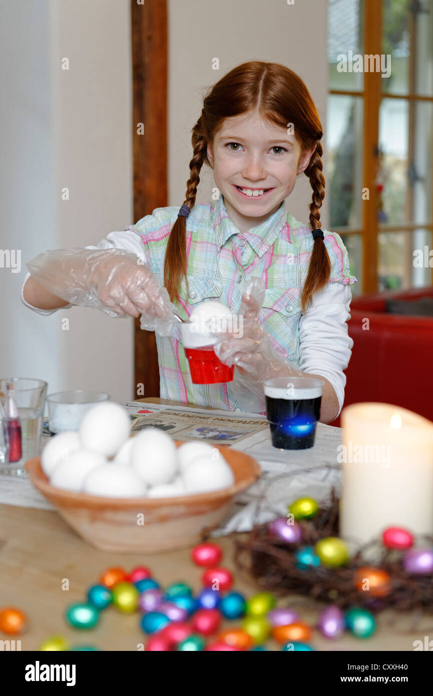 Child, girl colouring Easter eggs, Easter tradition - Stock Image