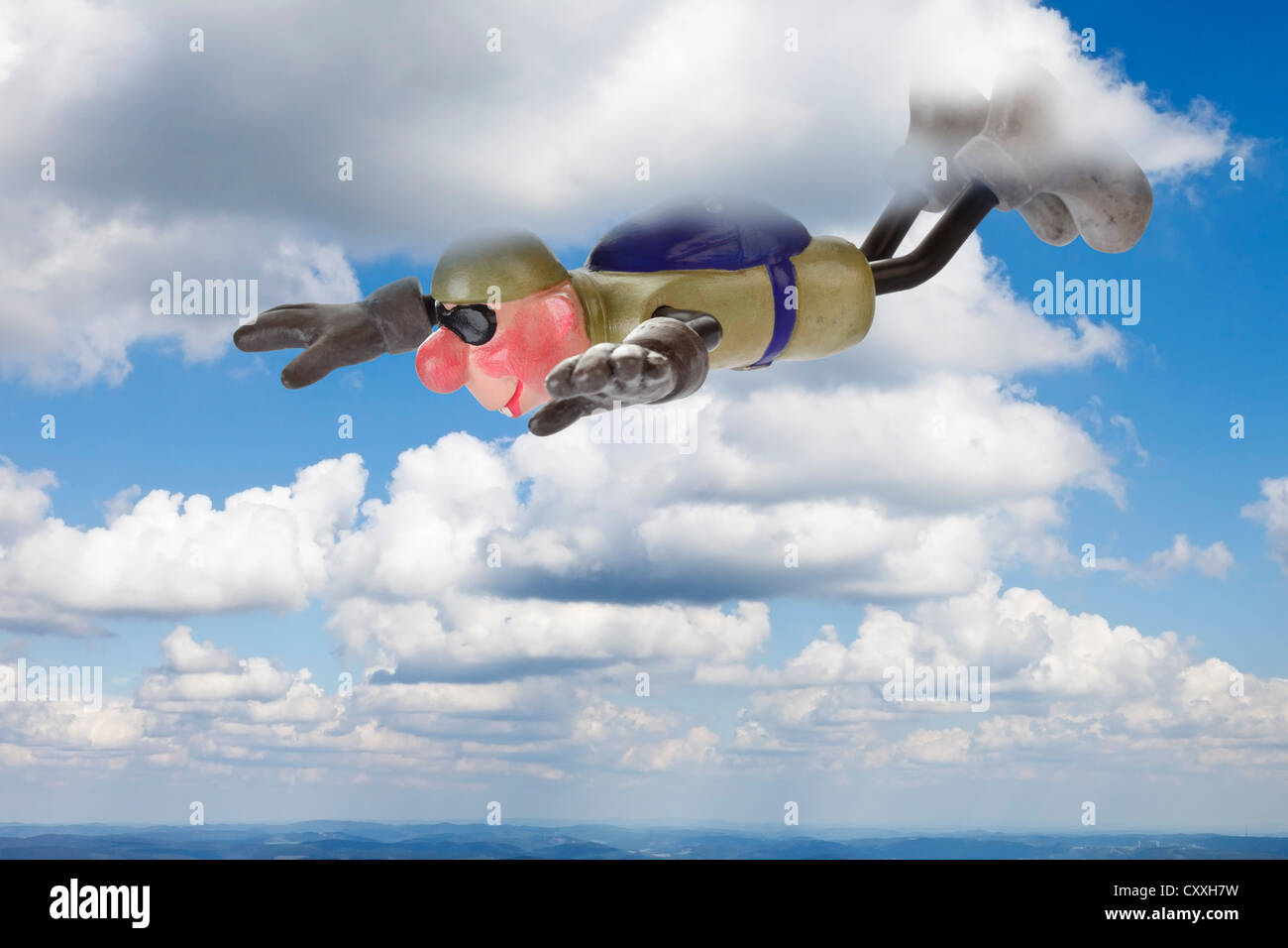 Cartoon character, basejumper in gliding flight through clouds - Stock Image