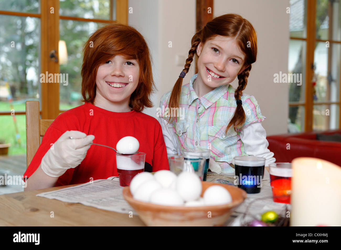 Boy and girl coloring Easter eggs, painting Easter eggs - Stock Image