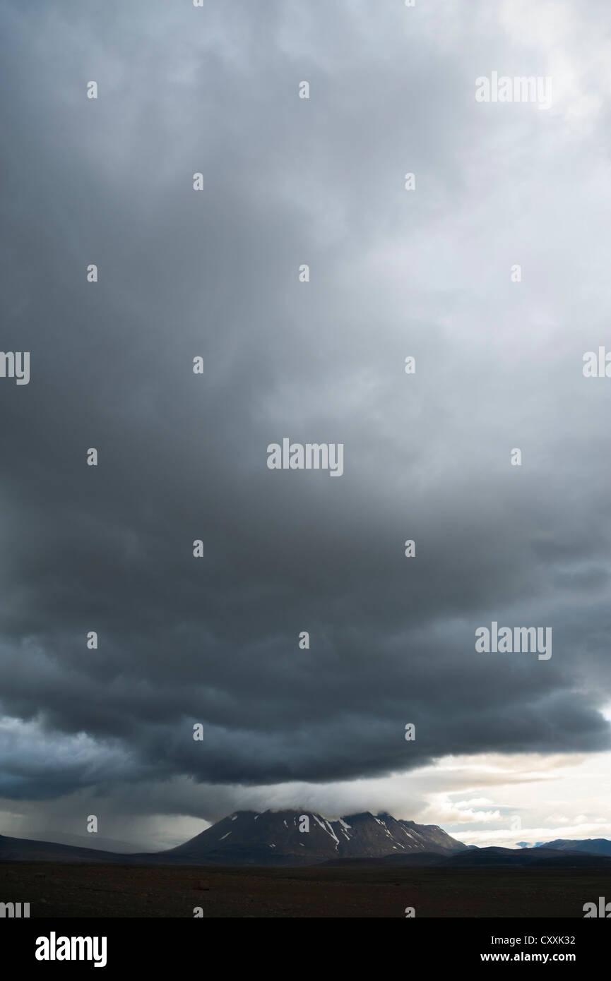 Bad weather, view towards snow-covered mountains and Langjoekull Glacier, highland slopes of Kjoelur or Kjalvegur, - Stock Image