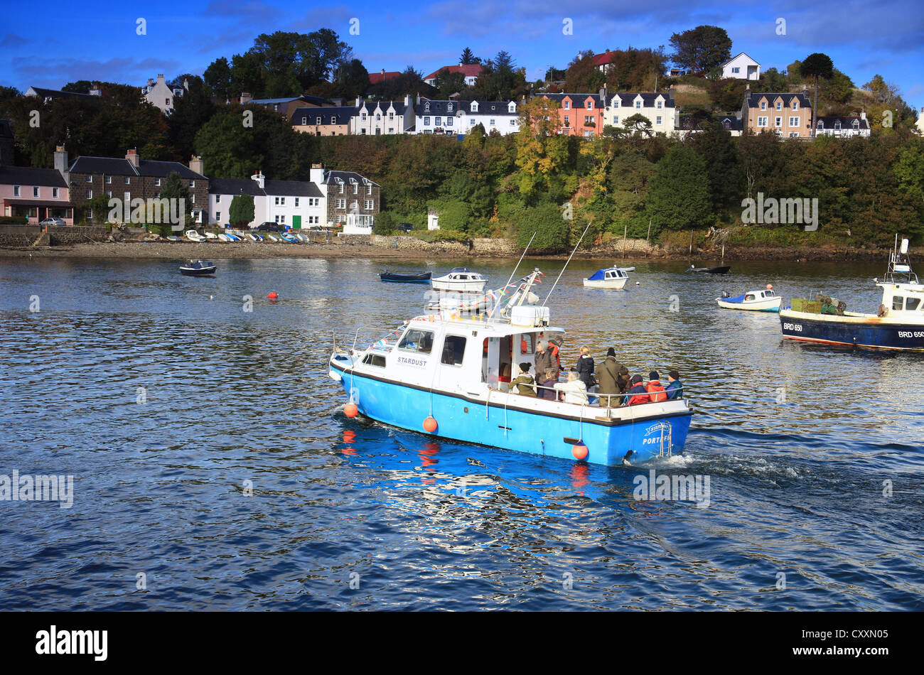 A colourful pleasure boat in the picturesque harbour of Portree on the Isle of Skye in the Scottish Highlands. - Stock Image