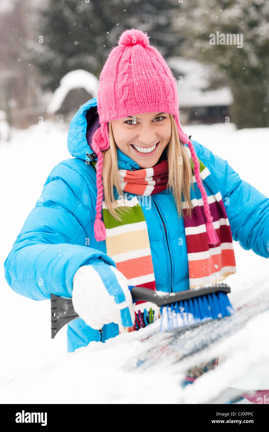 Woman wiping car windshield using brush snow winter happy work - Stock Image