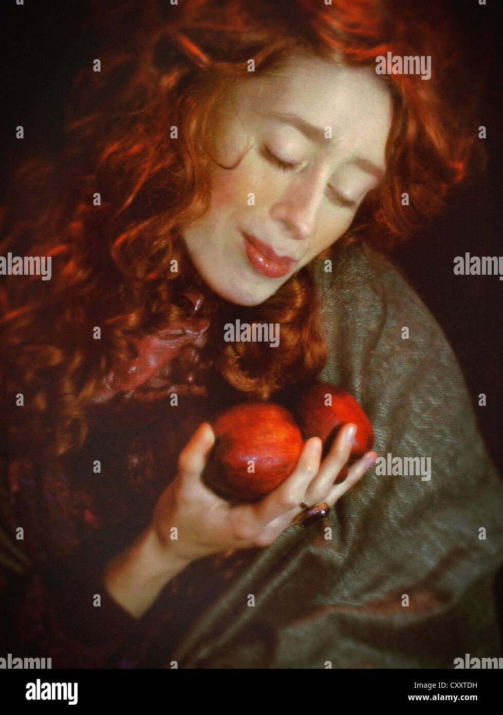 A woman in a scarf , with long red curls and red cheeks and lips, holding a pair of red apples. - Stock Image