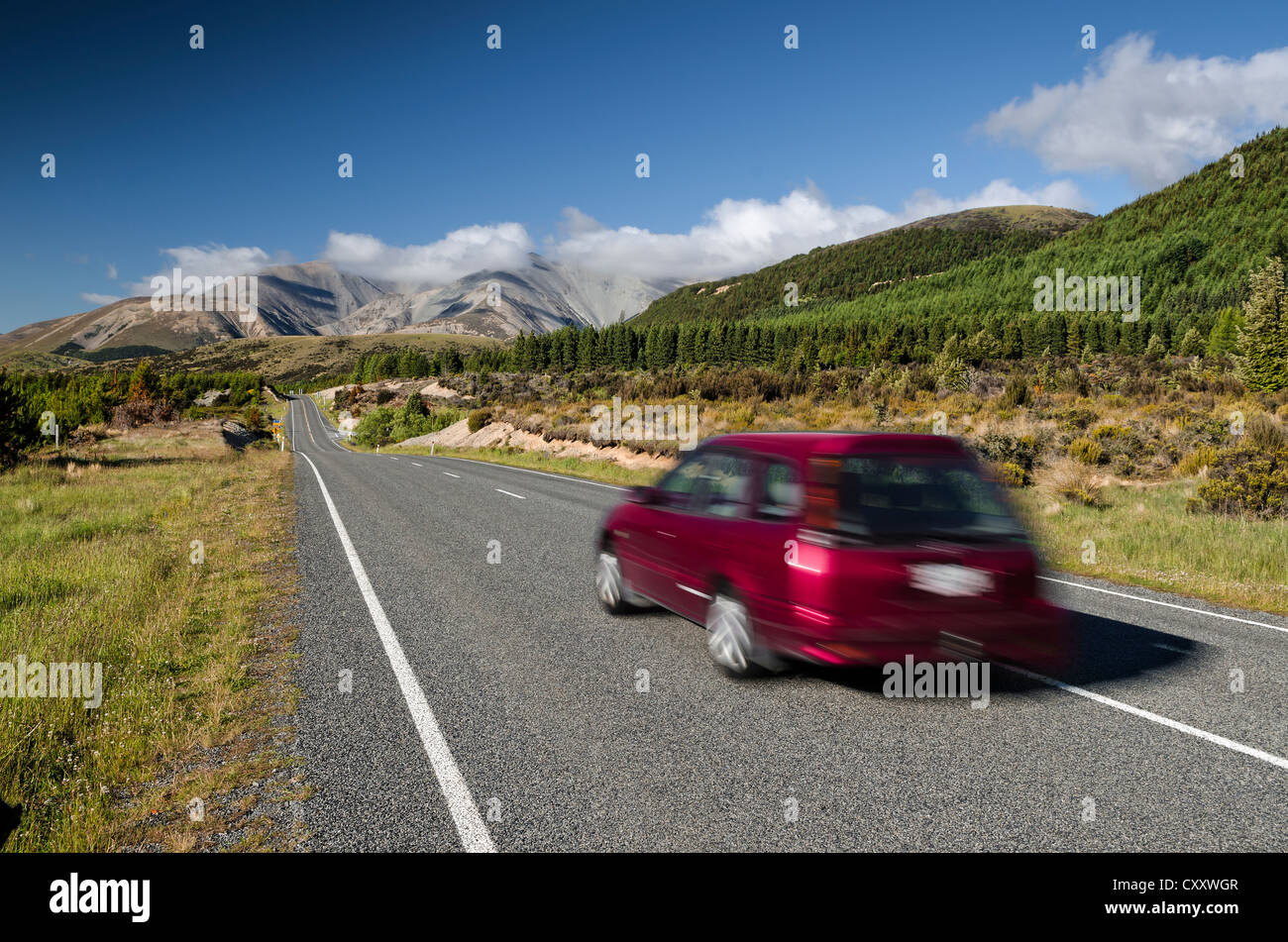 Red car driving on a country road, driving on the left, Arthur's Pass Road, South Island, New Zealand, Oceania - Stock Image