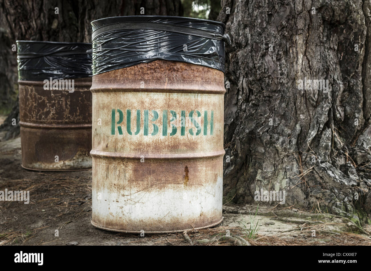 Rusty tin rubbish bin with word 'rubbish' next to a gnarled tree, New Zealand - Stock Image