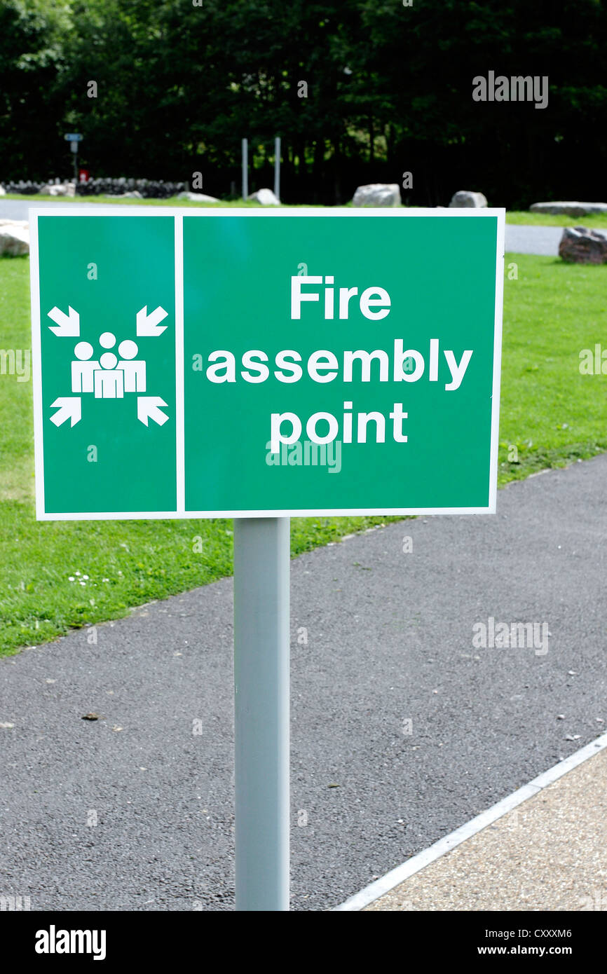 A sign denoting a Fire Assembly Point outside an office block. - Stock Image