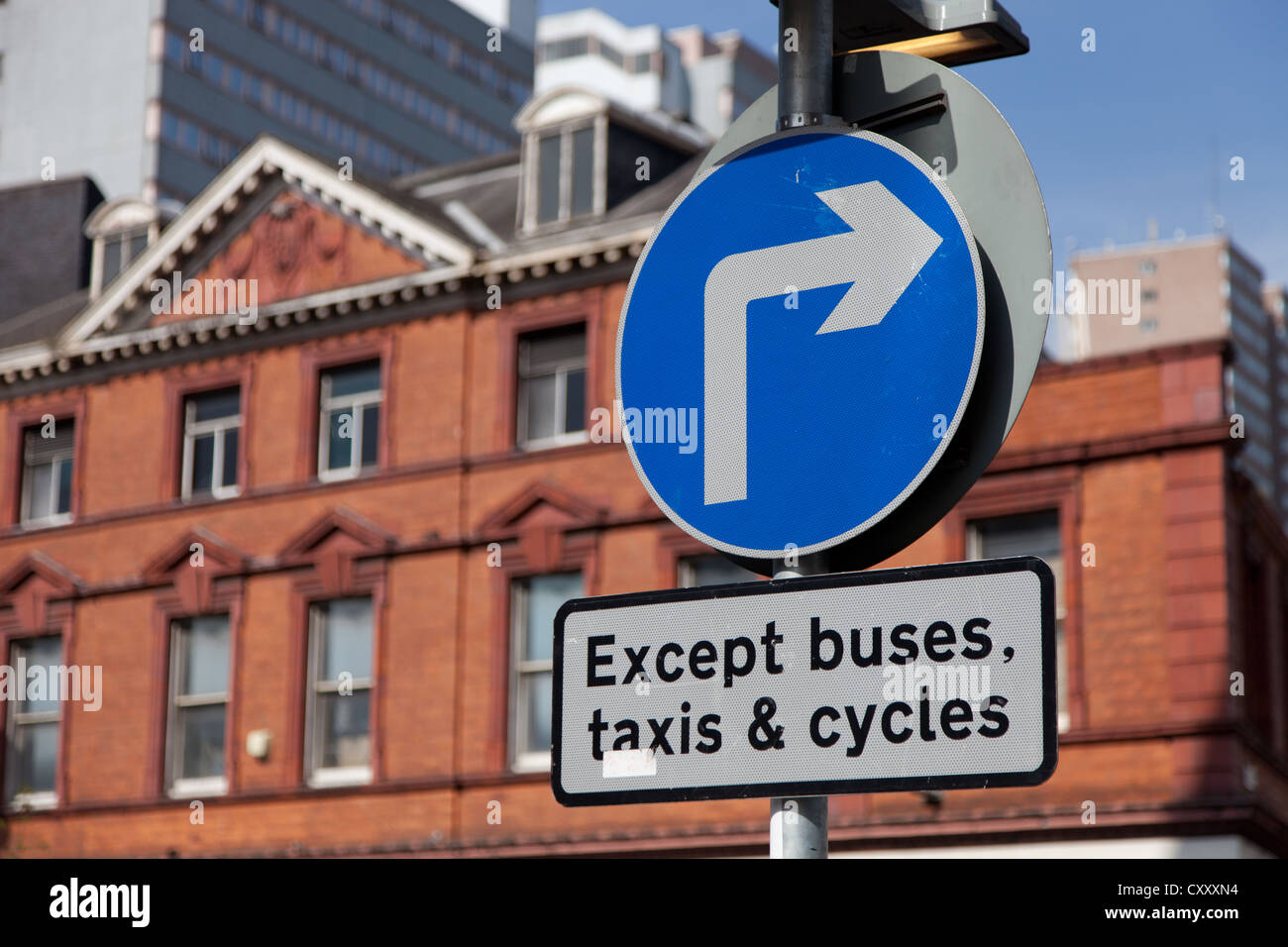 A road sign showing a compulsory right turn but with restrictions - Stock Image