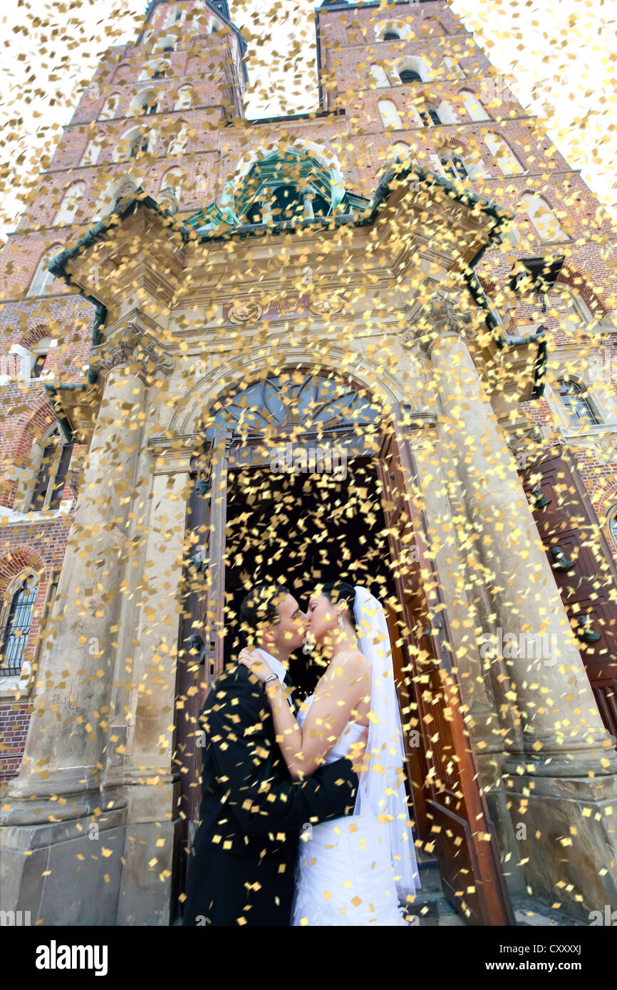 Bride and groom, bridal couple kissing in front of St. Mary's Church, confetti, Krakow, Poland, Europe - Stock Image