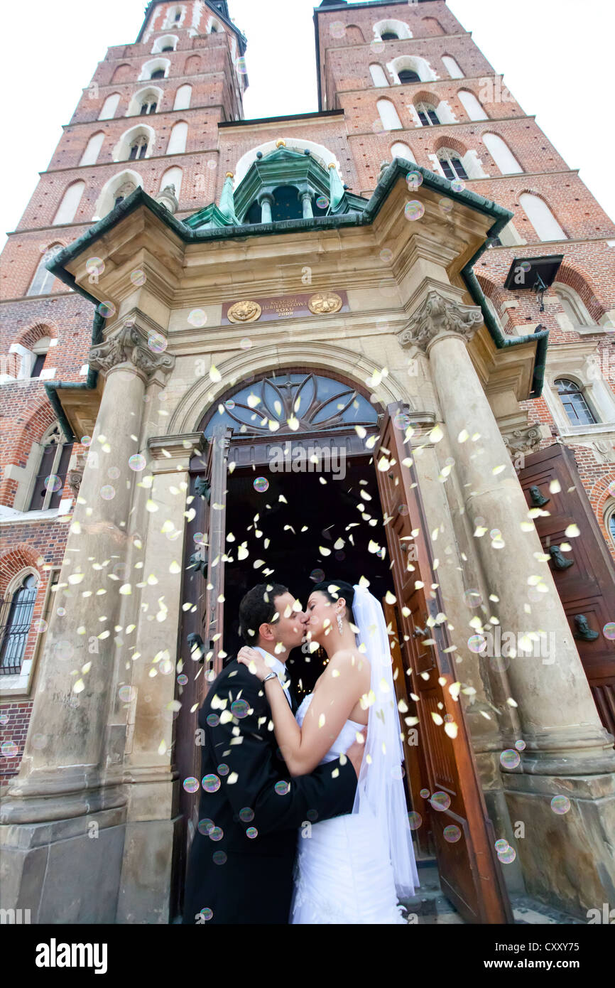 Bride and groom, bridal couple, kissing in front of St. Mary's Church, Krakow, Poland, Europe - Stock Image