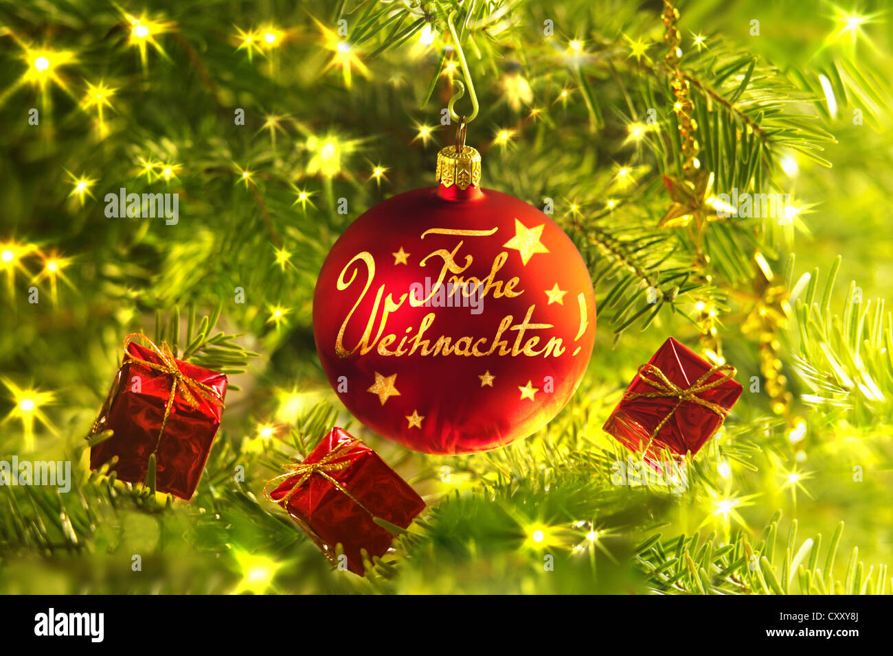 Red Christmas bauble with wording 'Merry Christmas' and small gift packs - Stock Image