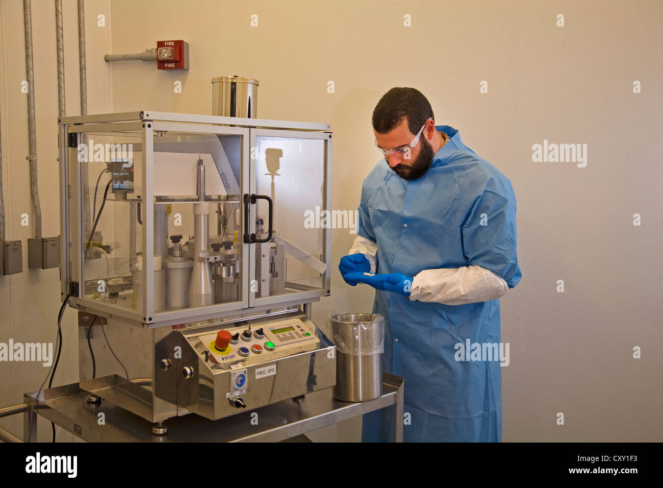 A chemist dressed in safety gear works in research at a at a pharmacutical research laboratory  - Stock Image
