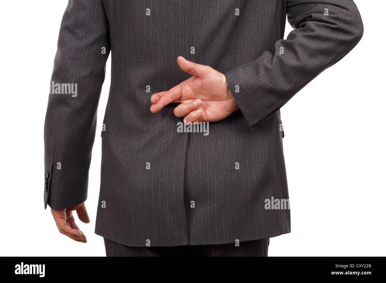 Fingers crossed behind businessmans back - Stock Image