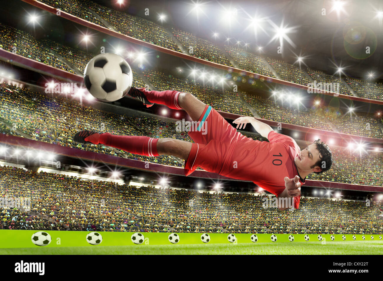 Soccer player jumping, kicking the ball, soccer stadium - Stock Image
