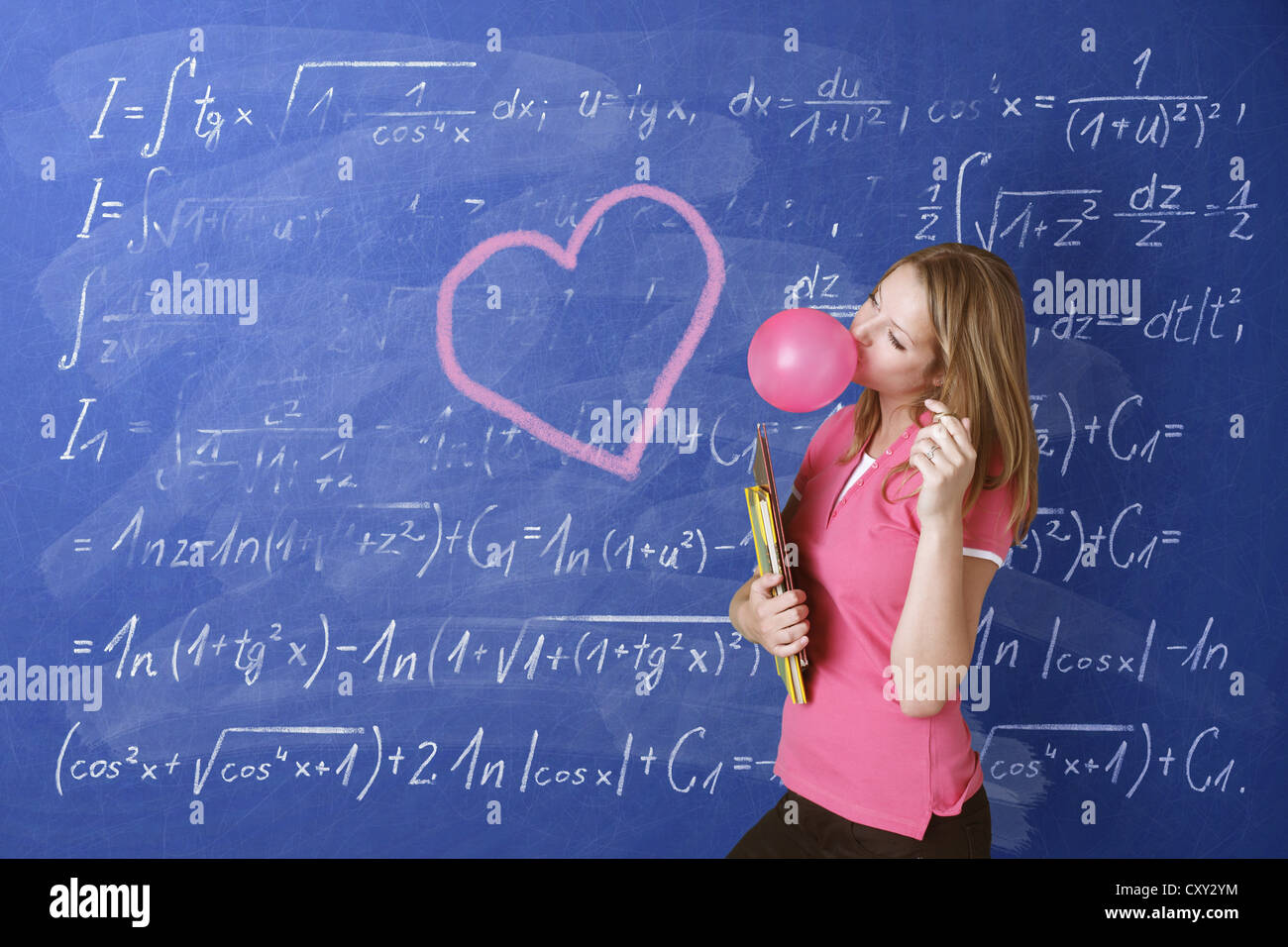Schoolgirl daydreaming while blowing a bubble with bubble gum in front of a school blackboard with a drawn heart - Stock Image