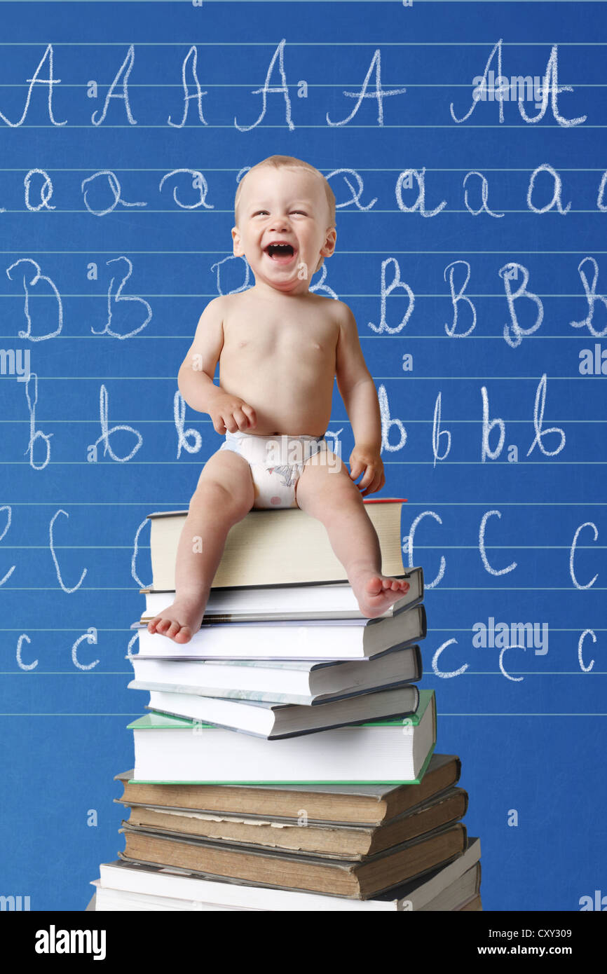 Laughing baby sitting on a pile of books in front of a blackboard with letters written on it Stock Photo