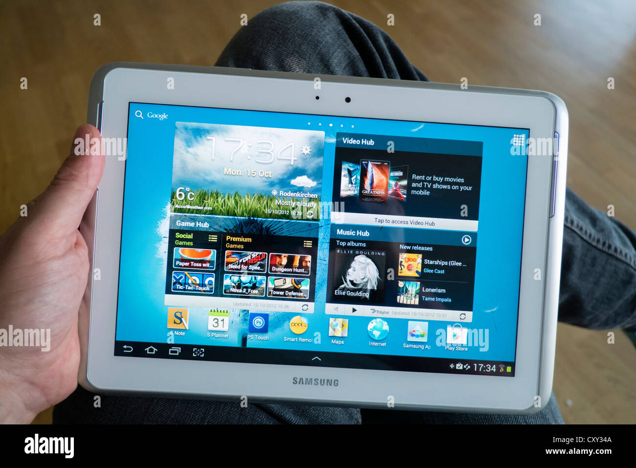 Man using Samsung Galaxy Note 10.1 tablet computer running Android operating system and showing large home screen - Stock Image