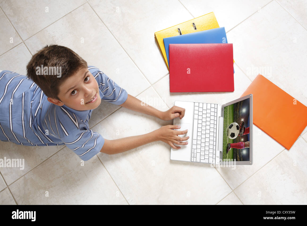 Young looking up while lying on the floor with a notebook, folders, and files - Stock Image