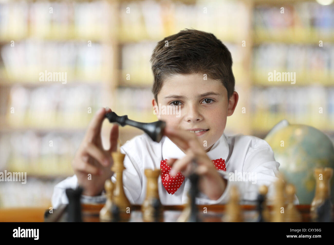 Boy considering a move while playing chess - Stock Image