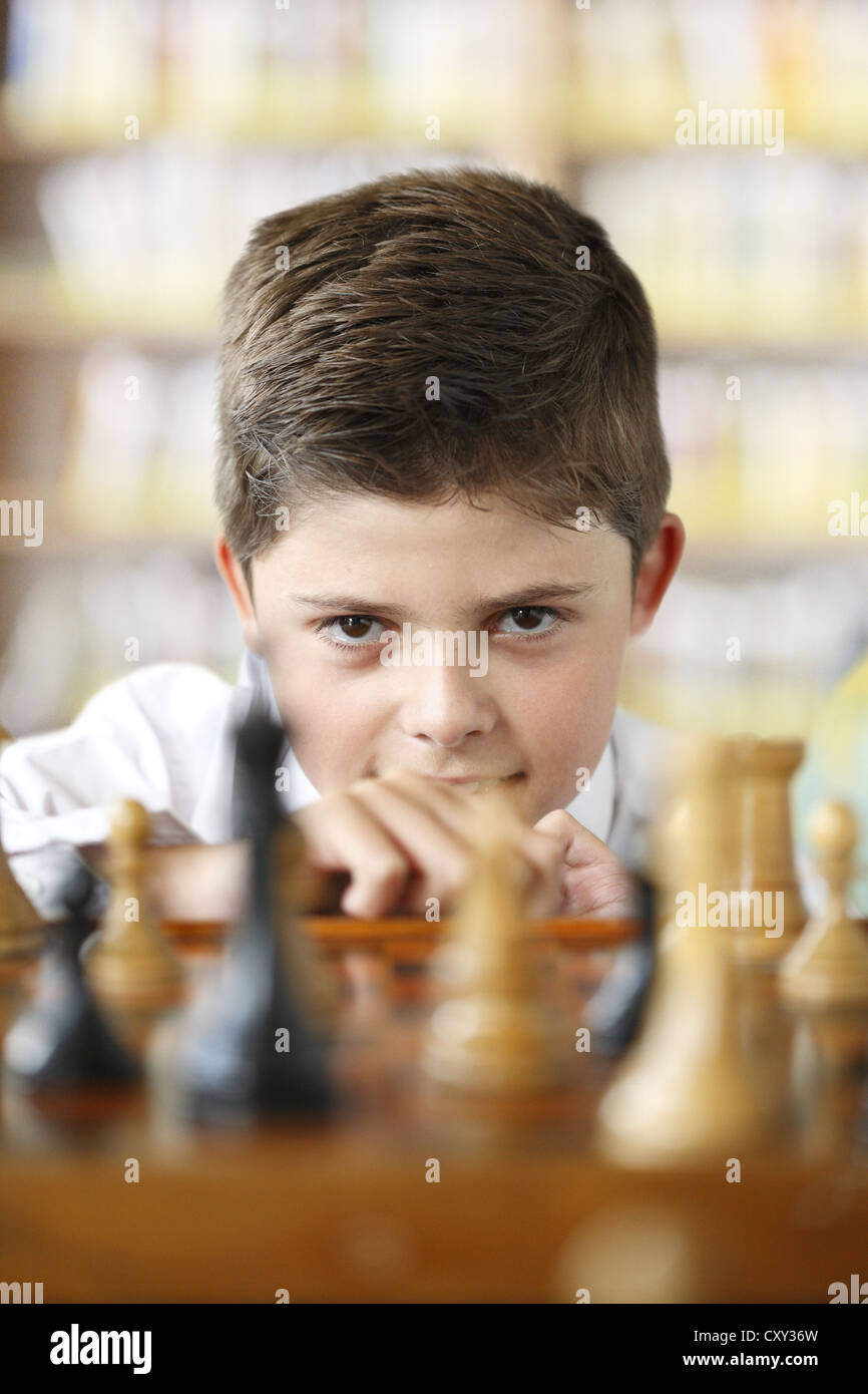 Concentrated boy playing chess - Stock Image