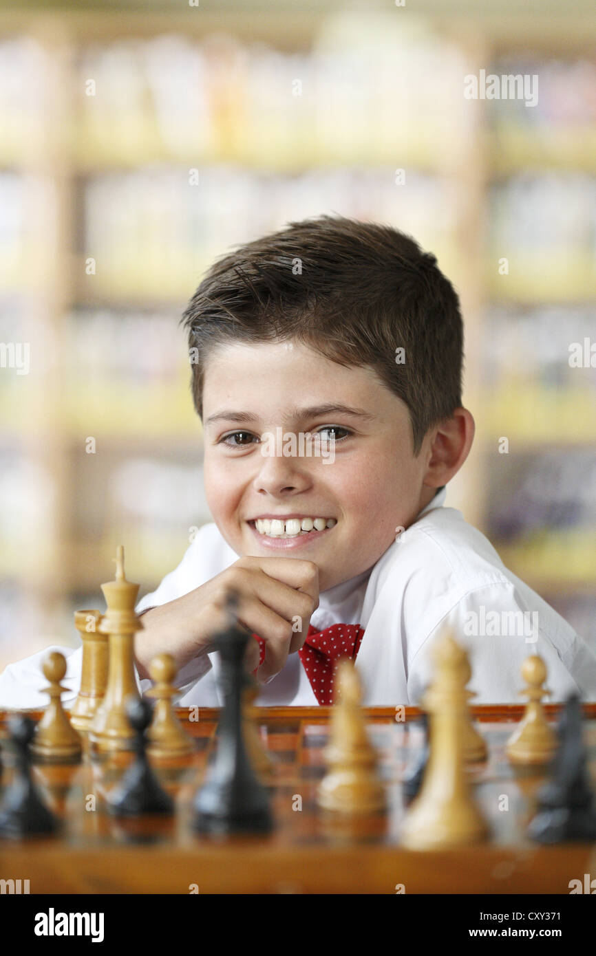Smiling boy playing chess - Stock Image