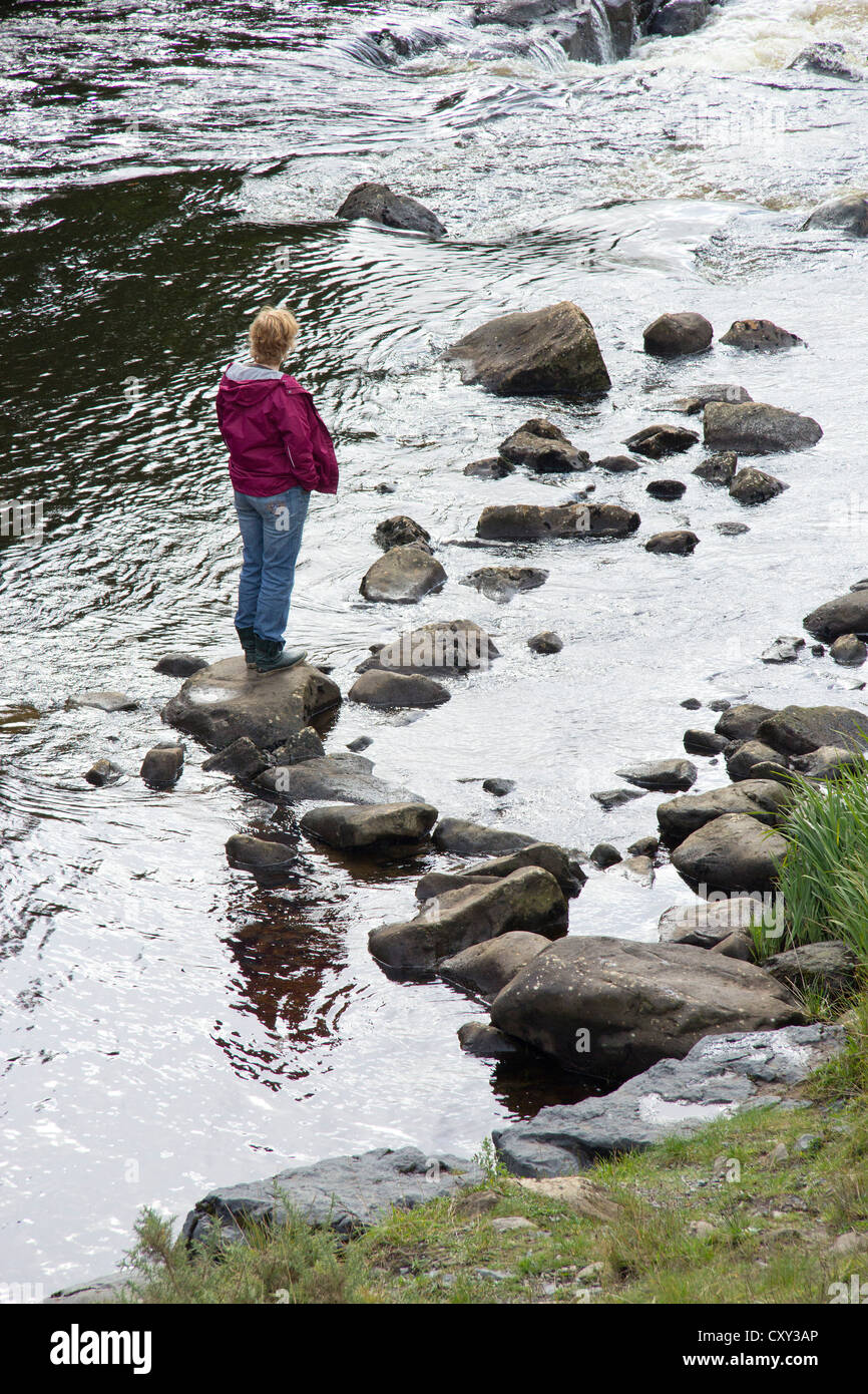 woman standing in a river near Leenane, Co. Galway Republic of Ireland - Stock Image