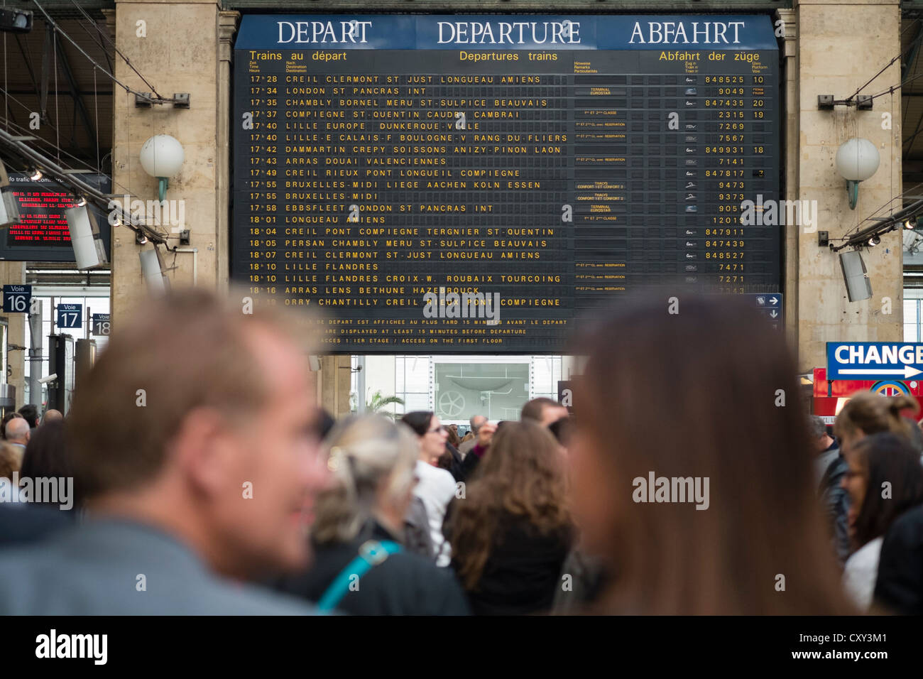 Detail of destinations on departures board and many passengers waiting for trains at Gare du Nord railway station - Stock Image