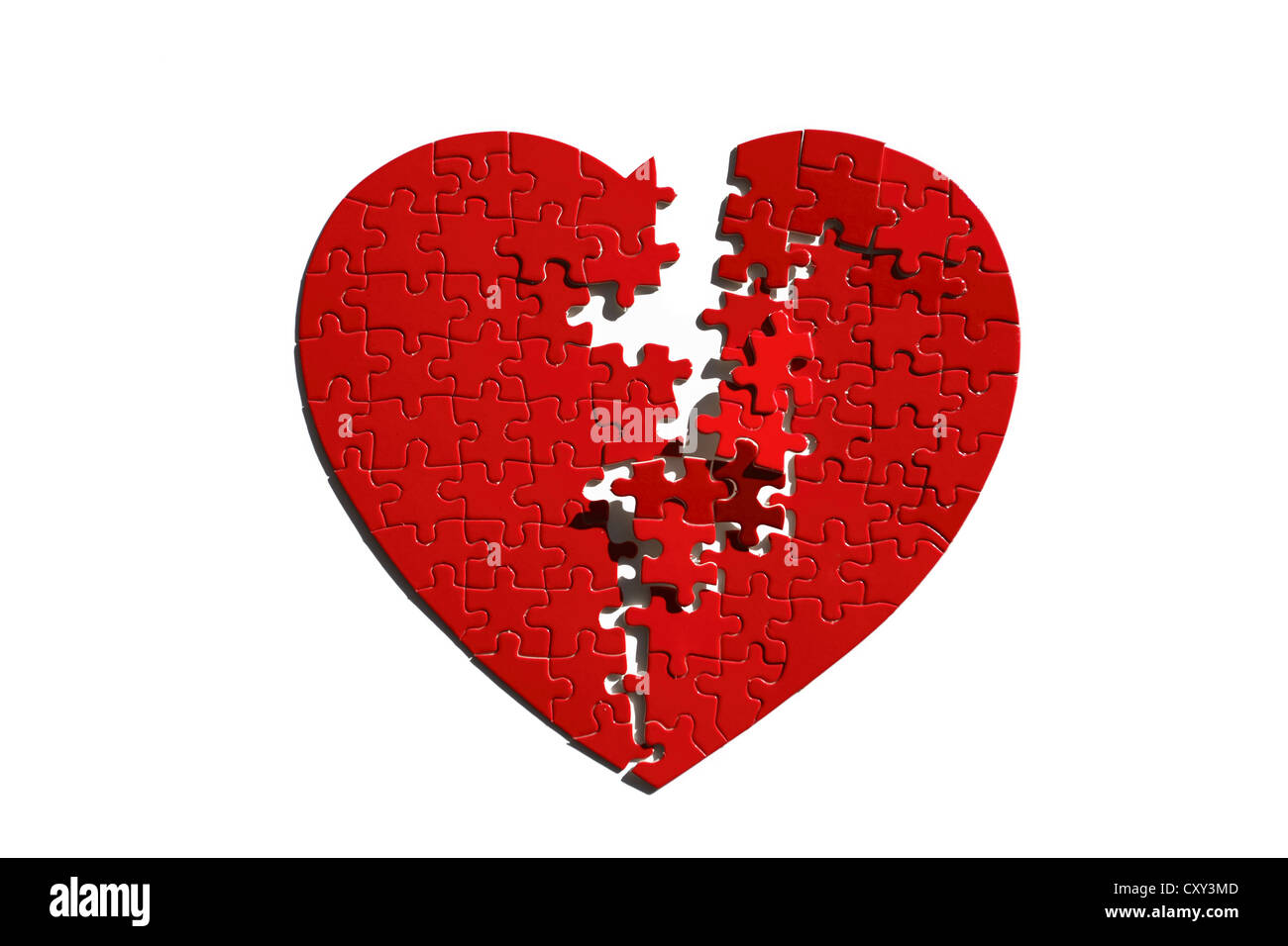 Red heart-shaped jigsaw puzzle, torn in half - Stock Image