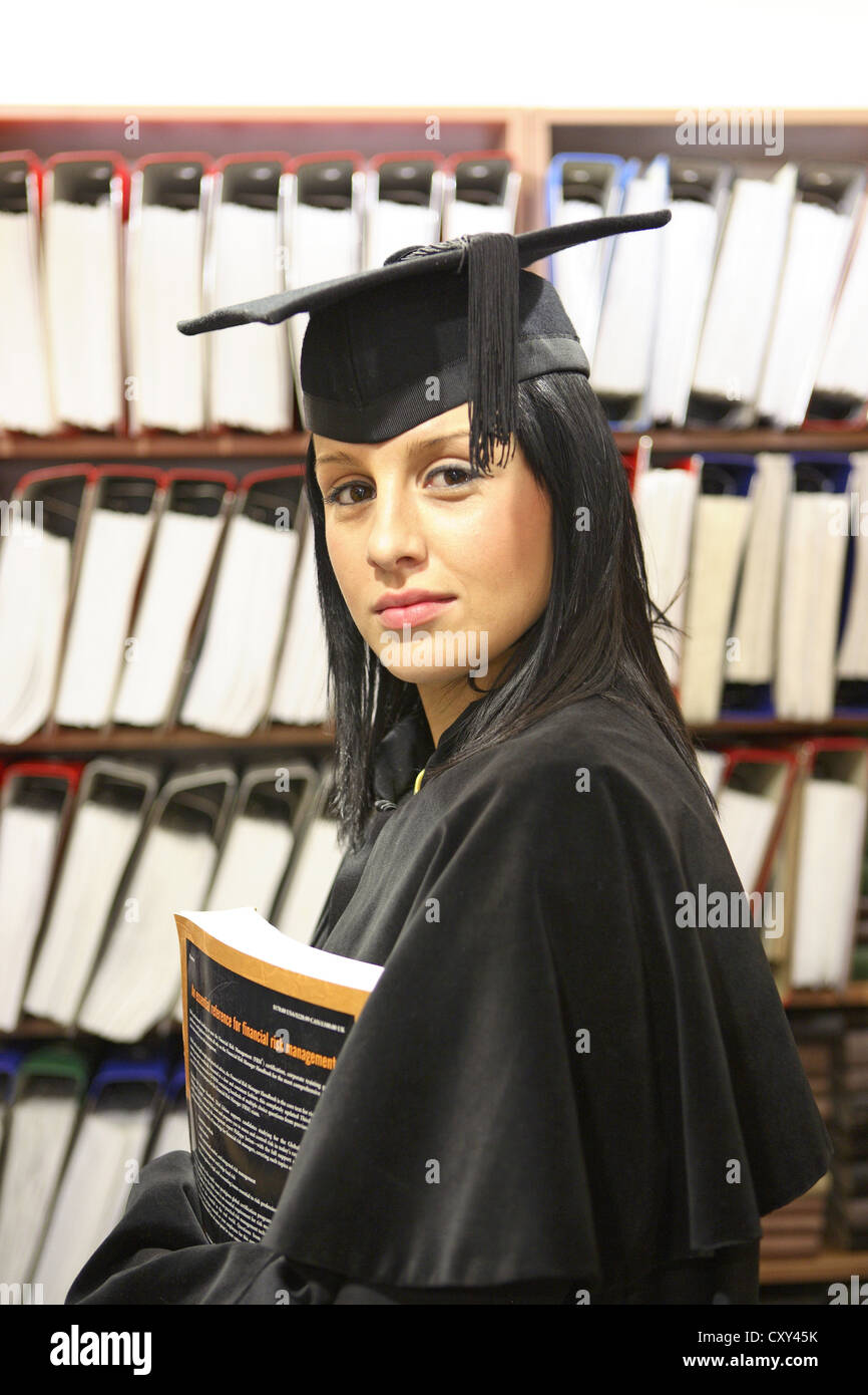 Female student wearing a graduation cap in front of a filing cabinet - Stock Image