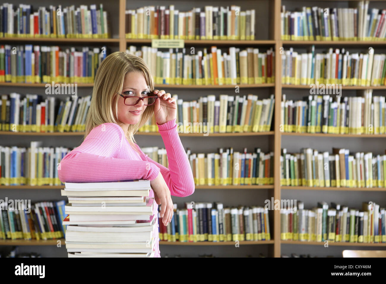 Female student wearing glasses with a stack of books in a university library - Stock Image