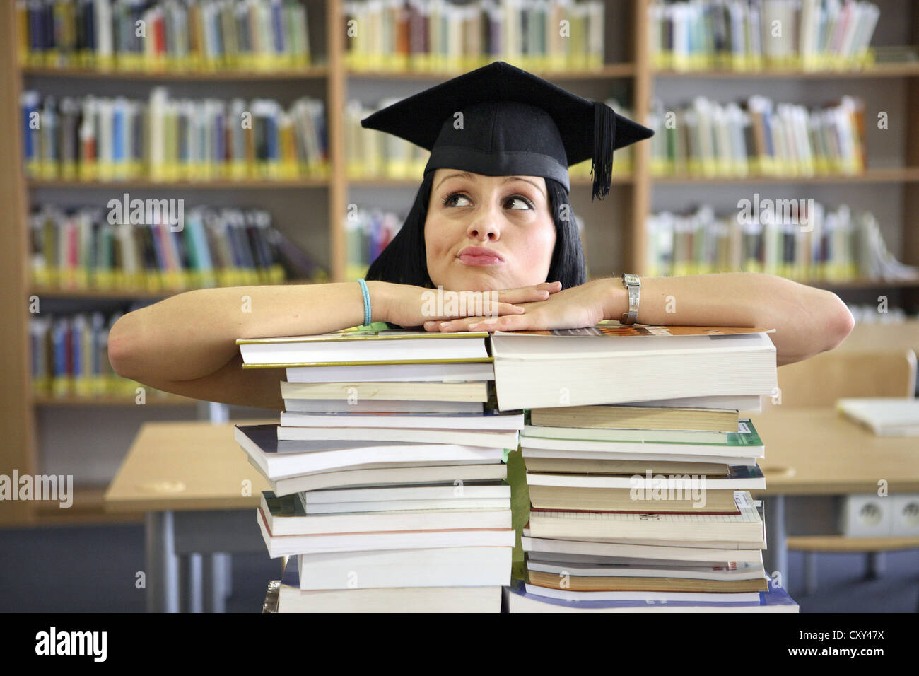 Skeptical looking female student wearing a graduation cap behind stacks of books in a university library - Stock Image