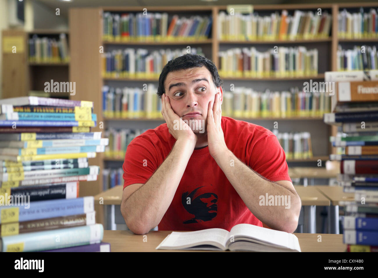 Student looking thoughtful in a university library - Stock Image