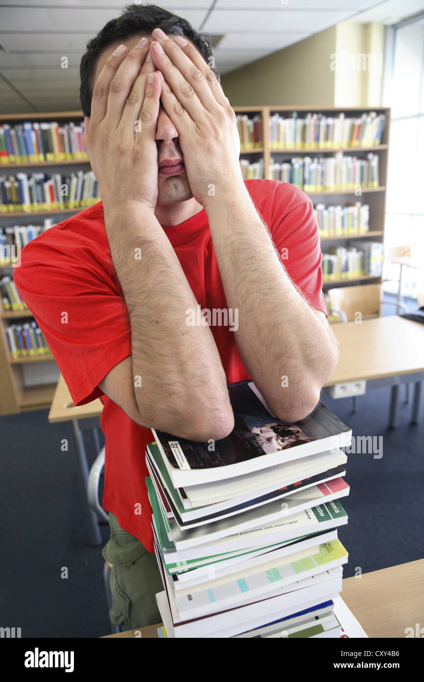 Desperate student with a stack of books in a university library - Stock Image