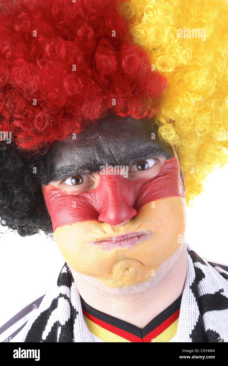 Football fan with their face painted and wearing a wig in the German national colours - Stock Image
