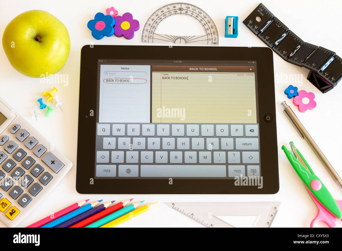 Ipad 3 with Notes application and school accesories on white - Stock Image