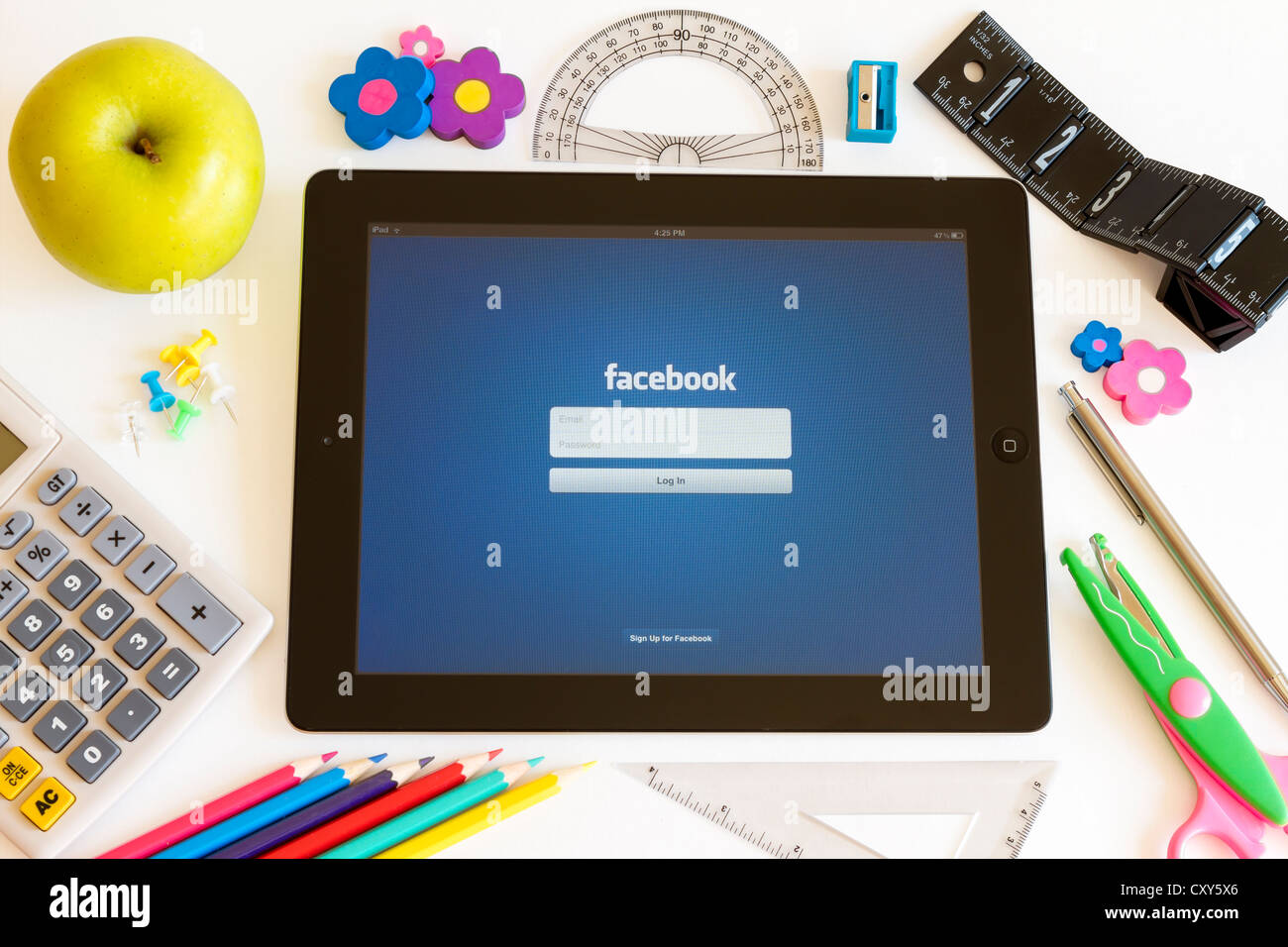 Facebook on Ipad 3 with school accesories on white background - Stock Image