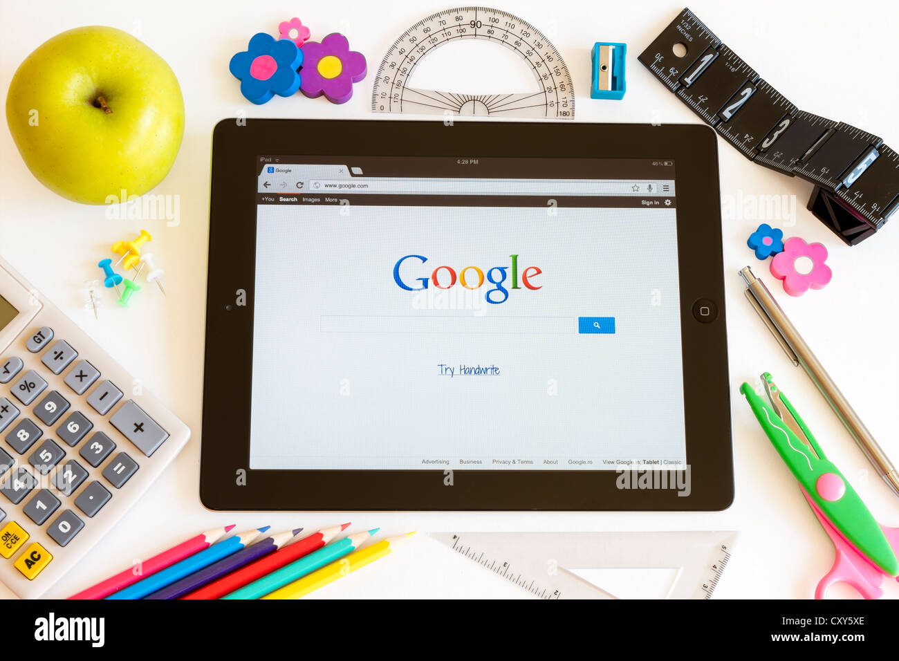 Google on Ipad 3 with school accesories on white background - Stock Image