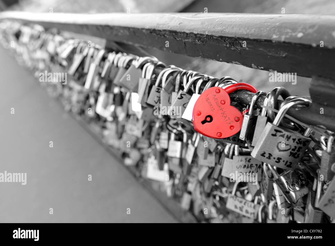 Lover's padlocks which adorn many bridges in Paris, France, red heart padlock monochrome background, love locks - Stock Image