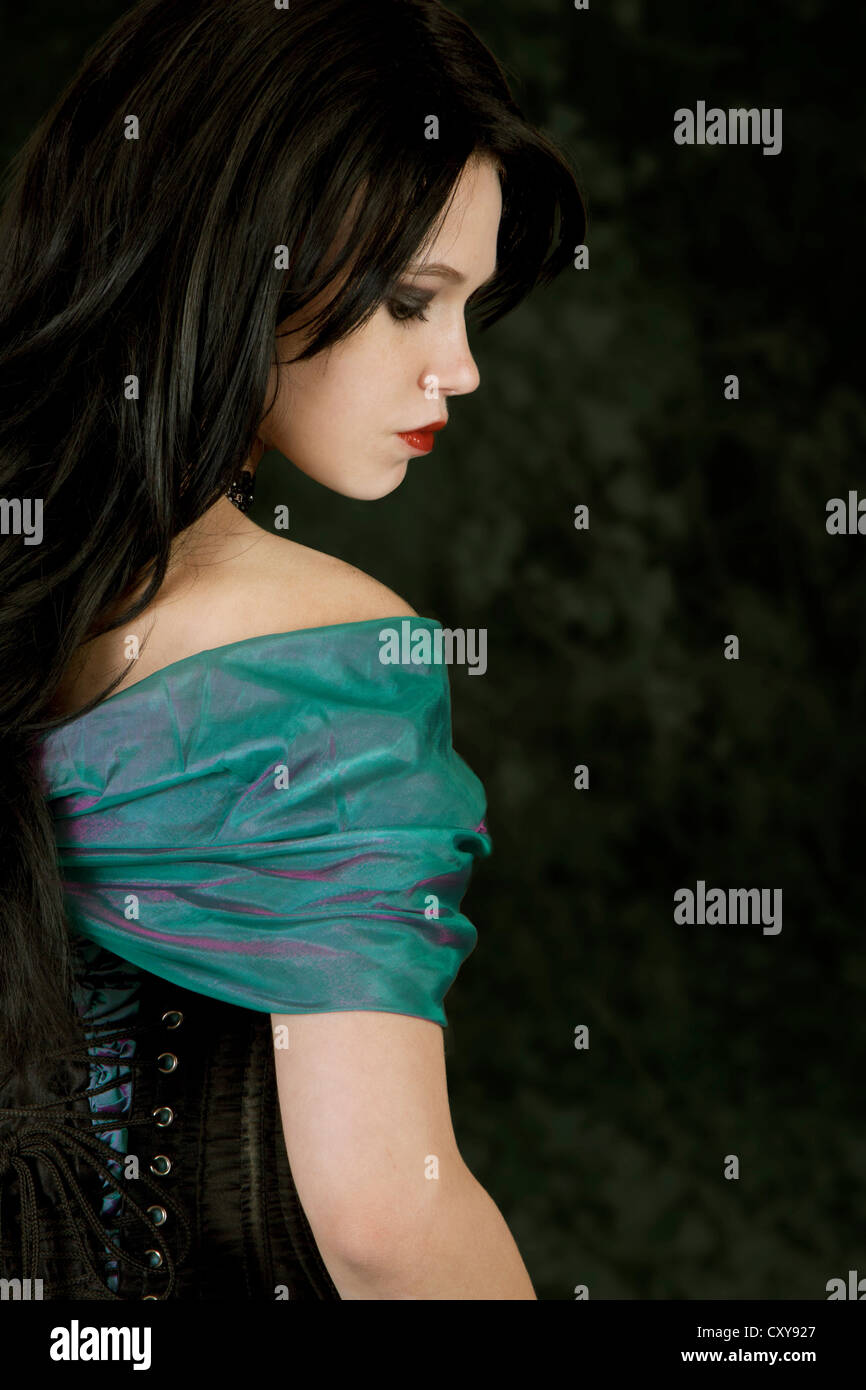 young adult with black hair and green dress Stock Photo