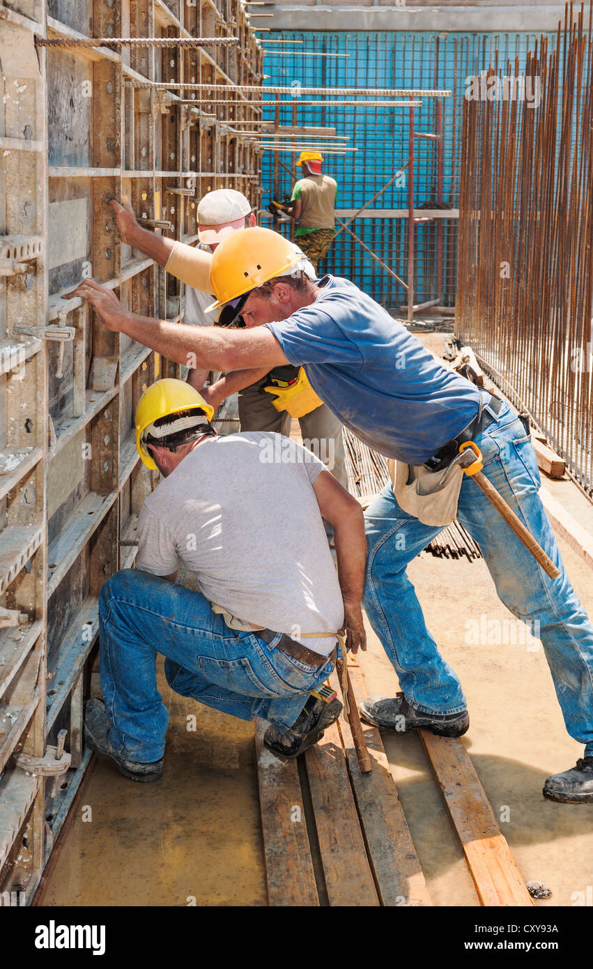 Construction builders positioning concrete formwork frames - Stock Image
