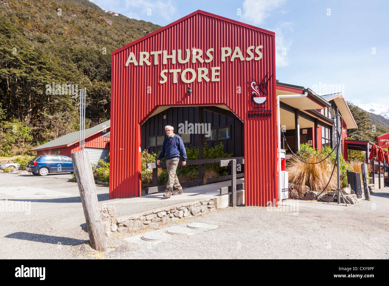 Arthurs Pass Store, Arthurs Pass, Canterbury, New Zealand, a man just walking out, on a bright sunny spring day. - Stock Image