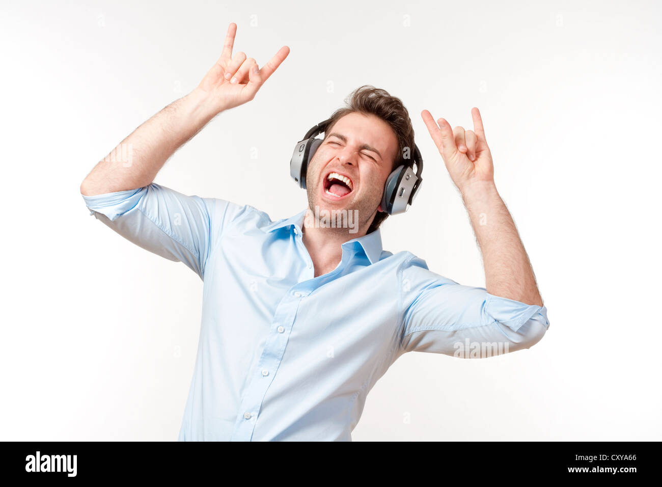 excited man in blue shirt with earphones listening to music - Stock Image