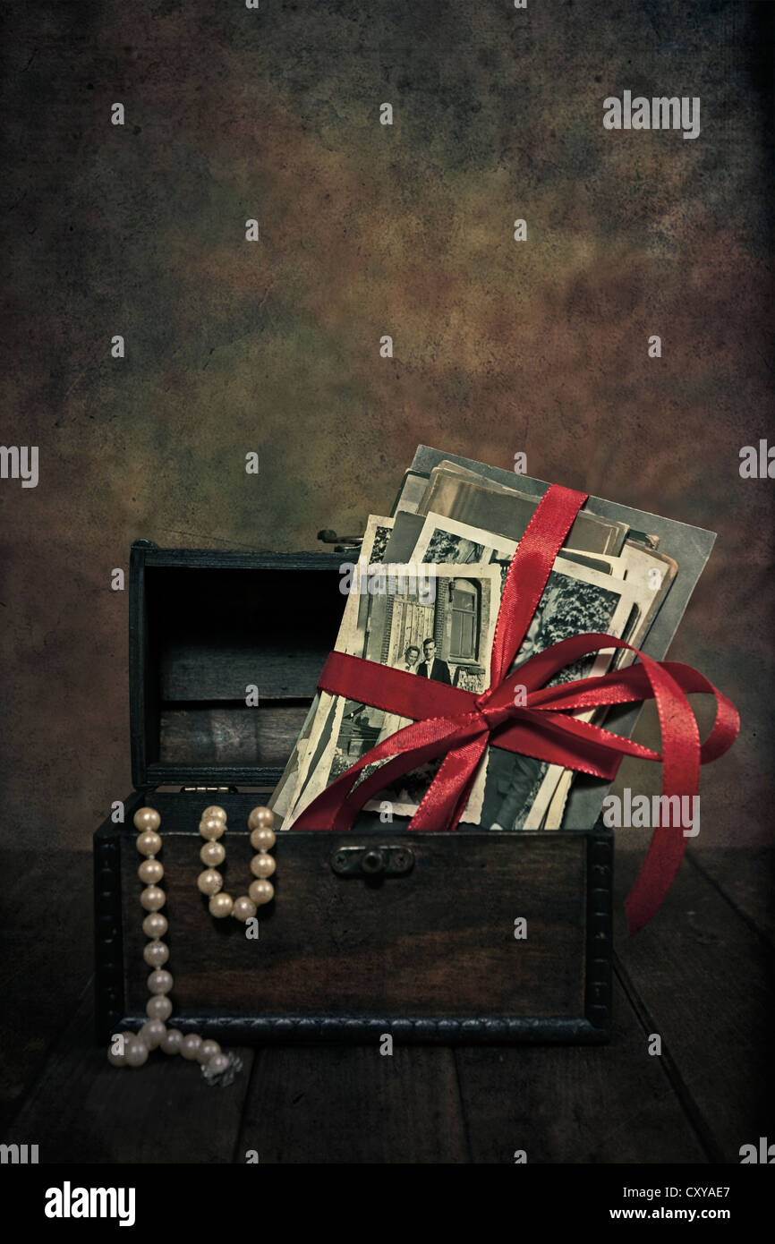 old photos with a bow in a chest with a pearl necklace Stock Photo